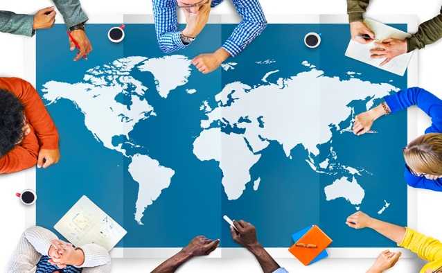 Table covered with a map of the globe, surrounded by people working